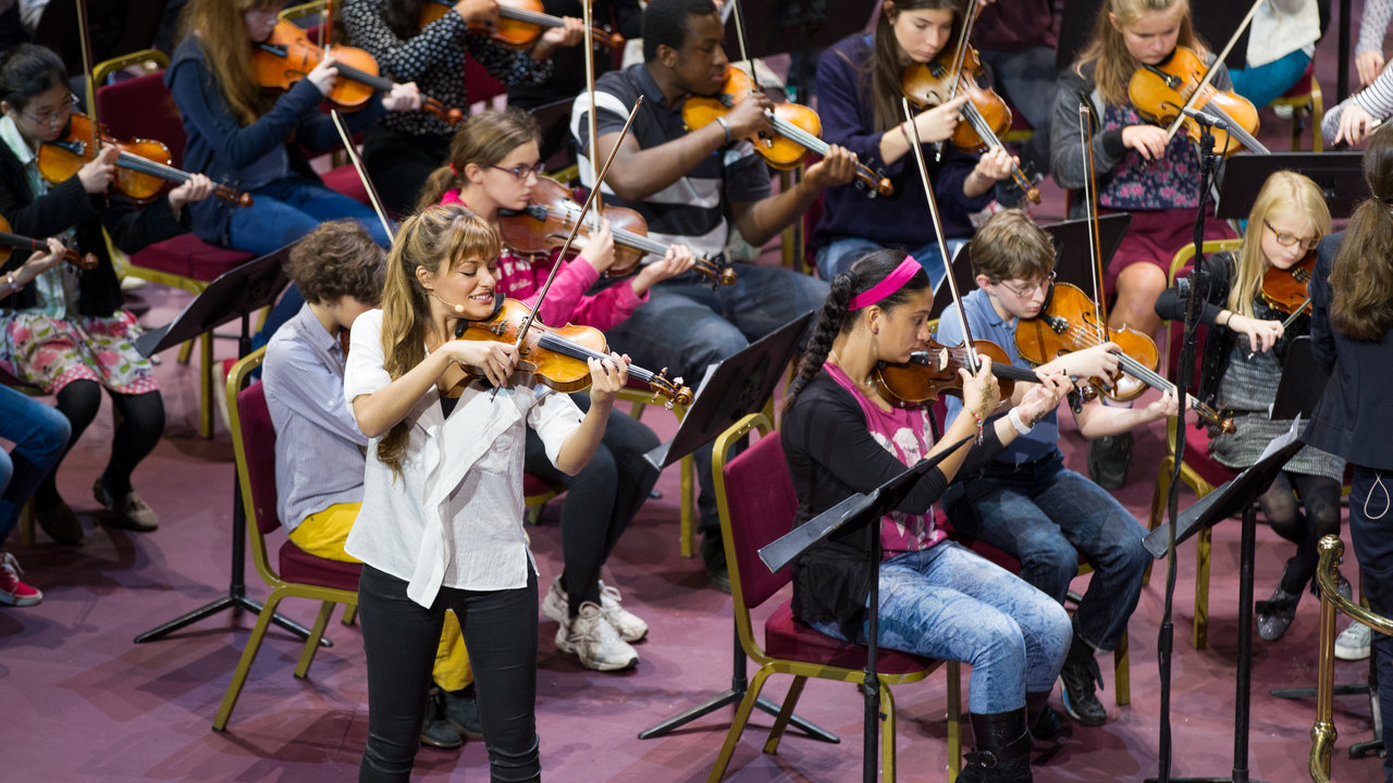 120 young violinists aged 7-16 rehearsing and performing with Nicola Benedetti in the main auditorium of the Royal Albert Hall.
