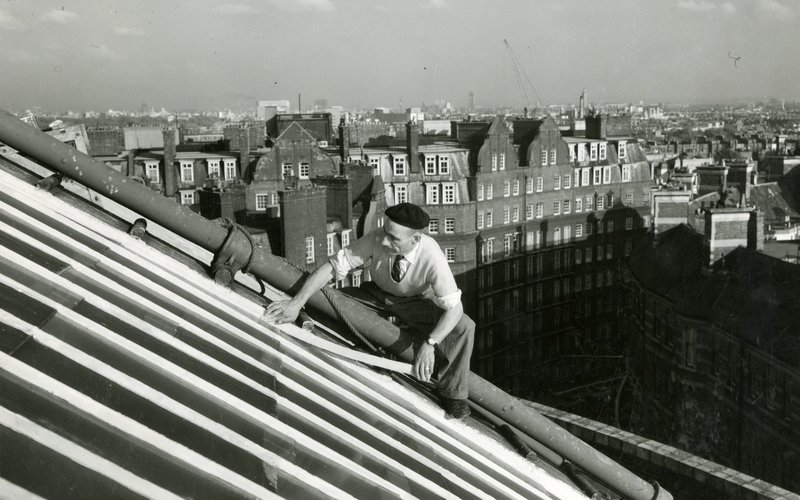 a worker undertaking post-war renewal work on the roof at the Royal Albert Hall